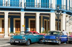 美国蓝色薛佛列敞篷车和薄荷的水星经典汽车在哈瓦那市古巴- Serie古巴报告文学的街道上停放了 免版税库存图片