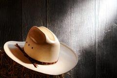 美国西方圈地牛仔草帽在老谷仓 库存图片