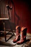 美国西部圈地女牛仔起动和老椅子 库存图片