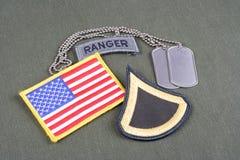 美国陆军一等兵茂盛的补丁、别动队员选项、旗子补丁和卡箍标记在橄榄绿unifor 图库摄影