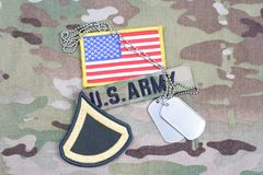 美国陆军一等兵茂盛的补丁,旗子补丁,与在伪装制服的卡箍标记 图库摄影