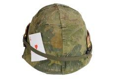 美国陆军盔甲与伪装心脏纸牌盖子和弹药传送带和护身符一点的越南战争期间  免版税库存图片