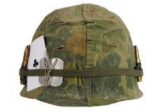 美国陆军盔甲与伪装盖子和弹药传送带、卡箍标记和俱乐部纸牌护身符一点的越南战争期间  免版税库存照片