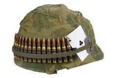 美国陆军盔甲与伪装盖子和弹药传送带、卡箍标记和俱乐部纸牌护身符一点的越南战争期间  库存图片