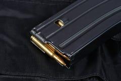 美国陆军M-16与弹药筒的步枪杂志在黑制服 免版税库存图片