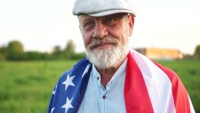 美国领抚恤金者庆祝美国独立日7月4日 有一个灰色胡子和盖帽的领抚恤金者拿着美国国旗 股票视频