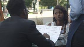 美国黑人的人预定在外部咖啡馆,当坐与他的女性伙伴时 库存图片