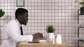 美国黑人的医生谈话与患者,在膝上型计算机的网上视频聊天 股票视频