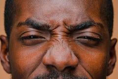 美国黑人的时髦的人半眯着的眼睛棕色演播室墙壁的 库存图片