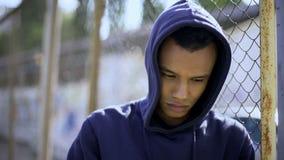 美国黑人的男孩倾斜在篱芭的,从不正常的家庭的年轻难民 免版税库存图片