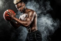 美国黑人的运动员,有一个球的蓝球运动员画象在黑背景 运动服的适合的年轻人 免版税库存照片