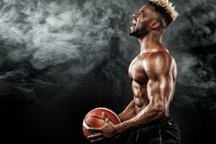 美国黑人的运动员,有一个球的蓝球运动员画象在黑背景 运动服的适合的年轻人 免版税图库摄影