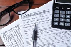 美国1040与玻璃、笔和计算器的报税表 免版税库存图片