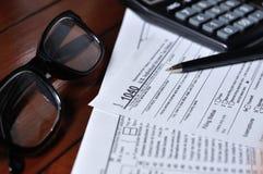美国1040与玻璃、笔和计算器的报税表 免版税库存照片
