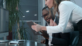 美国黑人的上司和他的使用数字式片剂的亚裔秘书 免版税图库摄影