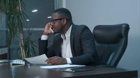 美国黑人的商人审查的图和谈话在电话 免版税图库摄影