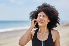 年轻美国黑人的在海滩笑的妇女听的audiobook 免版税库存照片