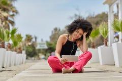 美国黑人的在片剂的妇女听的audiobook在海滩 免版税图库摄影