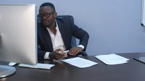 美国黑人的在他的智能手机的商人短信的电子邮件户内 免版税库存图片