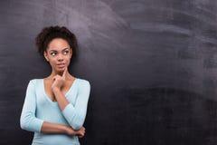 年轻美国黑人的妇女是近的黑板 免版税库存图片