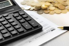 美国1040报税表、笔、计算器和硬币 免版税库存照片