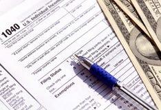 美国1040报税表、笔和美金 退还税金的概念 库存照片