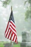 美国经验丰富的旗子在有雾的公墓 库存图片