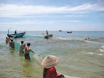 美奈海滩,越南- 2008年10月11日:当地渔夫扯拽与鱼捕获的捕鱼网从海洋 免版税库存照片