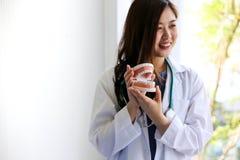 美女医生在脊椎的一根骨头指向膝盖关节的布局与患者的 库存图片