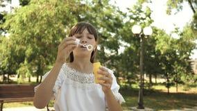 美女吹的肥皂泡在春天,夏天和微笑的公园 t 使用在的少女 股票视频