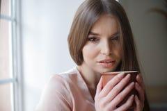 美女喝着坐在咖啡馆的咖啡和微笑的一会儿 免版税库存照片