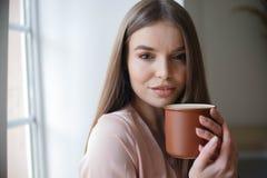 美女喝着坐在咖啡馆的咖啡和微笑的一会儿 免版税图库摄影