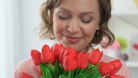 美女嗅到的郁金香,微笑入照相机,庆祝3月8日 股票视频