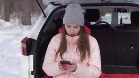 美女在一辆汽车坐在冬天森林里并且通过instagram看 股票录像