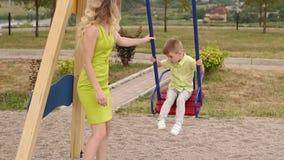 美女在摇摆滚动她的一点儿子在公园在夏天 股票录像