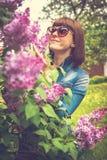 美女在有开花的丁香的春天庭院里 E beauvoir 免版税库存图片