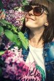 美女在有开花的丁香的春天庭院里 E beauvoir 免版税库存照片