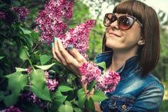 美女在有开花的丁香的春天庭院里 E beauvoir 库存图片