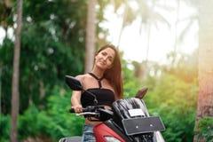 美女在阳光下和驾驶在棕榈树背景的脚踏车红色  免版税库存照片
