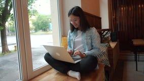 美女坐与便携式的网书的在现代咖啡厅,年轻迷人的女性自由职业者 股票视频