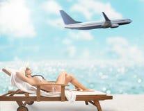 美女坐轻便折叠躺椅在海滩在与飞机的日落在背景 免版税库存照片