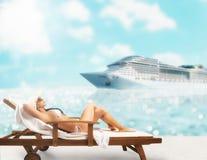 美女坐轻便折叠躺椅在海滩在与cruiseship的日落在背景 库存照片