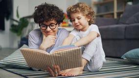 美女对笑小的男孩的慈爱的父母看书谈话和 股票录像