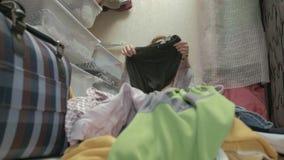 美女是沮丧的,一个疲乏的年轻母亲把从篮子的衣裳扔出去在她的化装室 放置 股票录像