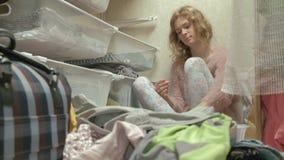 美女是沮丧的,一个疲乏的年轻母亲把从篮子的衣裳扔出去在她的化装室 放置 影视素材