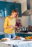 美女照片一个自创饼 有片剂的现代主妇在厨房 免版税库存图片