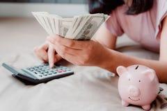 美女特写镜头是计算节约金钱,当说谎在她的卧室时 财政的事务和投资概念 免版税图库摄影