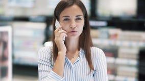 美女画象化妆商店谈话的在电话,慢动作 影视素材