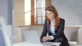 美女研究膝上型计算机的在昂贵的办公室,负责任的雇员 免版税库存照片