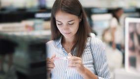 美女选择在化妆用品的唇膏购物,看标签,慢动作 股票录像